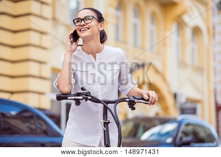 Call me back soon. Positive charming delighted woman standing near bicycle and talking on cell phone while expressing joy