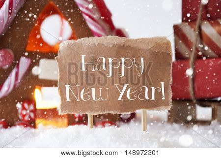 Gingerbread House In Snowy Scenery As Christmas Decoration. Sleigh With Christmas Gifts Or Presents And Snowflakes. Label With English Text Happy New Year