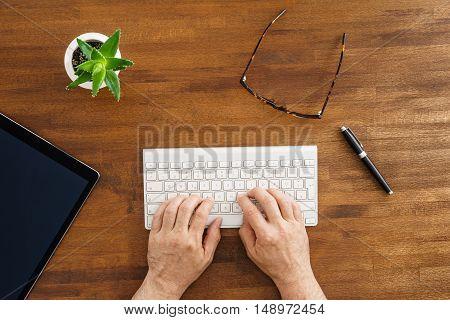 Man typing on keyboard on wooden desktop