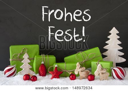 German Text Frohes Fest Means Merry Christmas. Green Gifts Or Presents With Christmas Decoration Like Tree, Moose Or Red Christmas Tree Ball. Black Cement Wall As Background With Snow.