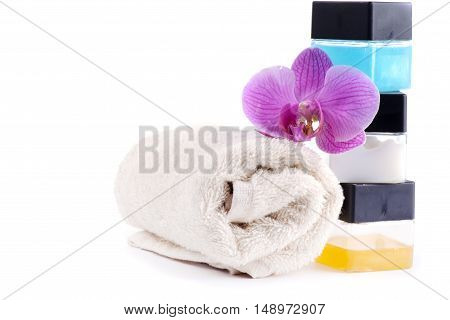 Stack of spa accessories with flower and towel isolated on white