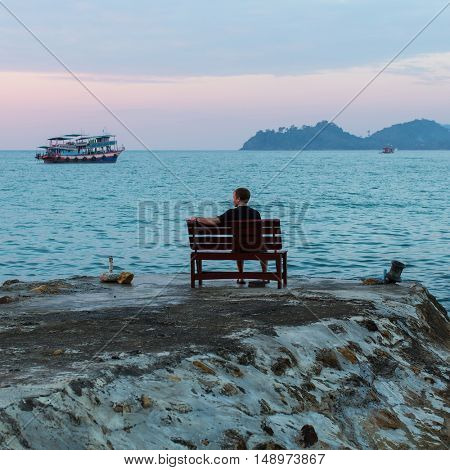 Lonely man sitting on a bench looking at the sea after sunset.