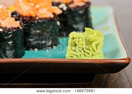 Wasabi with baked sushi rolls made from black rice and salmon, served on turquoise plate. Shallow depth of field. Focus on the wasabi.