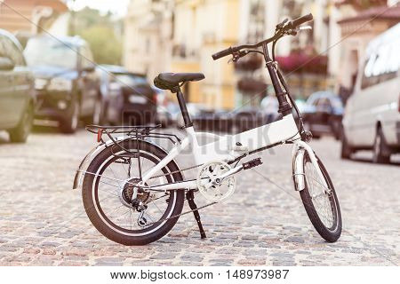 Quick and nature friendly. Modern bicycle standing on the road in the street of the city