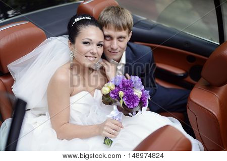 Wedding couple is hugging in a car. Beauty bride with groom. Beautiful model girl in white dress. Man in suit. Female and male portrait. Woman with lace veil. Cute lady and guy outdoors