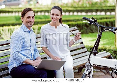 Smile and cope with it. Smiling handsome man and young happy woman preparing their work after cycling in the park and using the laptop.