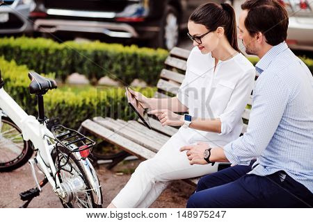 Share your best ideas. Young successful woman showing her great ideas to her handsome colleague using a tablet while sitting in the park.
