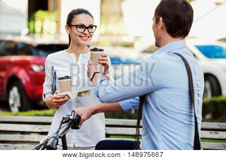Enjoy your coffee. Nice cheerful woman giving a cup of hot and strong coffee to her colleague while he is using a bicycle before going to work