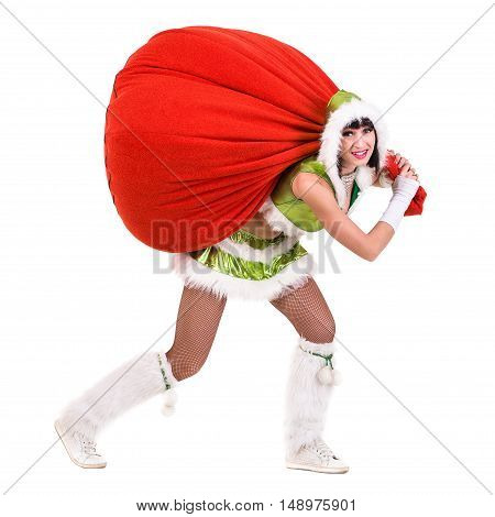 Woman dressed like a funny gnome pulls red bag with gifts. Isolated on white background in full length.