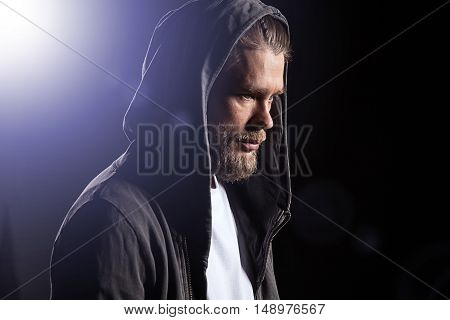 Portrait of a Man in a hoodie with a hood thrown over his head on a black background with light beam