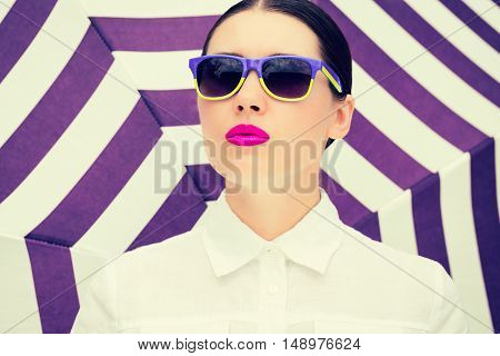 Portrait of a pretty young woman with colorful sunglasses and bright painted lips next to striped background