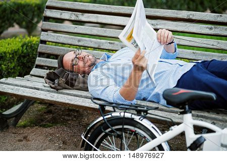 Relaxation on the bench. Handsome grizzled happy man reading newspaper and smiling while lying on bench .