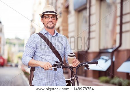 Be trendy. Positive delighted fashionable adult man drinking coffee ad walking along the street with his bike nearby
