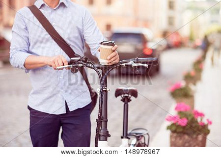 Like such time spending . Pleasant man standing with bicycle and drinking coffee while walking in the city
