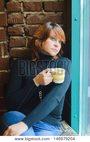 redhead woman thinking while sitting in a cafe