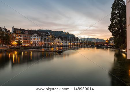 Sunset over the waterfront Lucerne Switzerland with the orange glow of the sky and lights in the buildings reflected in the calm water of the lake in a scenic landscape view