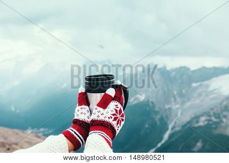 Closeup photo of thermos mug with tea in traveler's hand over out of focus mountains view with snow, tourizm in cold season