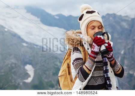 Traveler drinking tea in thermos mug in mountains with snow, winter hiking