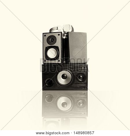 Image of three audio speakers in a wooden case and headphones. Photo black and white toned isolated on a light background with reflection on a horizontal surface. There is an empty seat for your text.