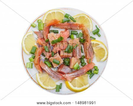 Cold-smoked salmon on a plate with lemon and green onion