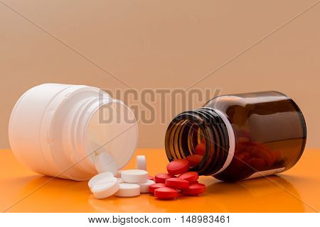 Heap of round colored tablets and pills bottle