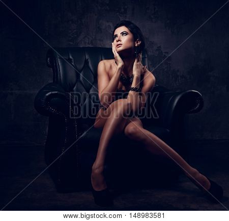 Sexy Woman In Fashion Dress Posing In Luxury Black Armchair And Looking Up. Dark Dramatic Shadow Lig