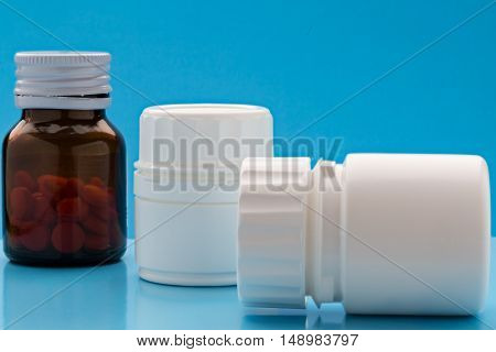 Various plastic and glass pills bottle on blue bacground