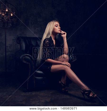 Sexy Slim Blond Model Sitting In Fashion Armchair In Black Dress And Posing On Dark Background. Art