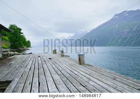 pier for boats on the shore of the fjord with the rocky shores