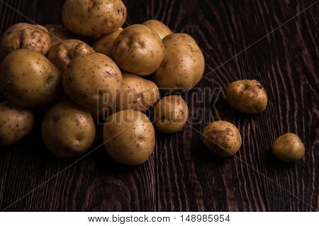Freshly grown potato on wooden table