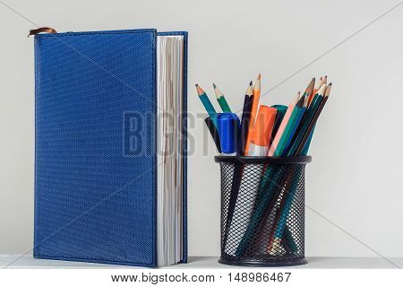 Stand up blue notebook and colored pencils with markers in black metal office stand on white background