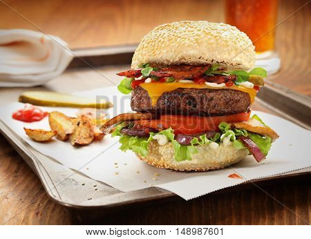 Gourmet burger with potatoes and beer on a wooden table