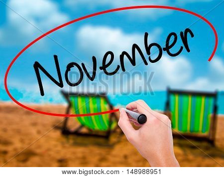 Man Hand Writing November With Black Marker On Visual Screen