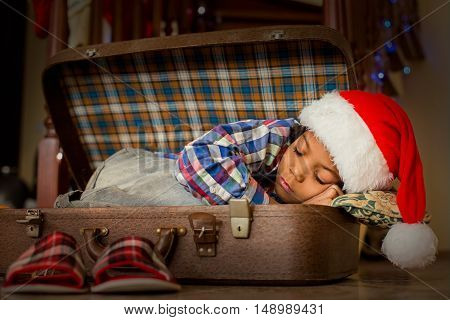 Kid sleeping inside cozy suitcase. Boy's Christmas nap inside suitcase. Little Santa needs some rest. Cozy place to sleep in.