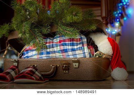 Child's Christmas sleep inside suitcase. Kid sleeping beside Christmas decorations. Charming holiday atmosphere. Presents are waiting.