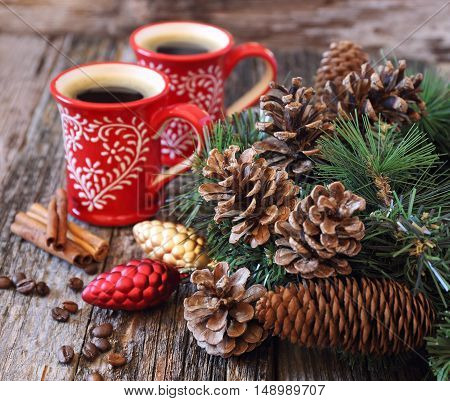 Two cup of coffee pine cones and New-Year tree decorations on a wooden background