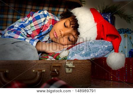 Boy's Christmas nap beside presents. Afro kid sleeping near presents. Wake up and celebrate. Happiness is waiting for you.