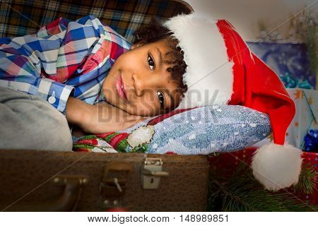 Smiling little Santa beside presents. Christmas kid laying near presents. Happiness delivery at your service. Magic moments of holiday.