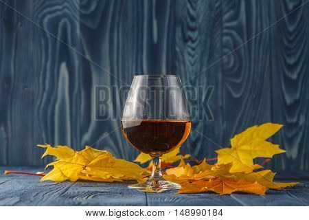 Glass Of Whiskey On Table With Leaves