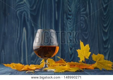 Cognac Glass With Dried Autumn Leaves On The Table