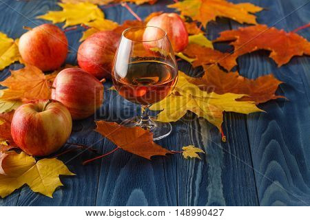 Alcohol drink and autumn leafs with apples