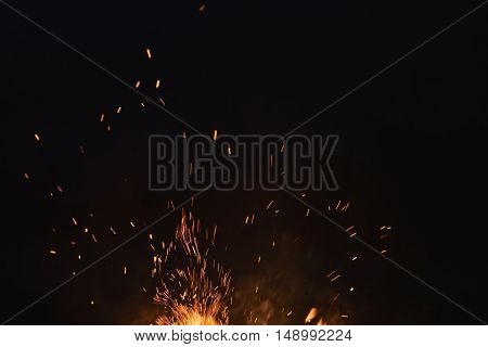 firecamp sparks over night sky, black background