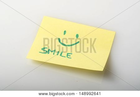 paper notepad with a smile written and drawn a smile that express the concept of happiness