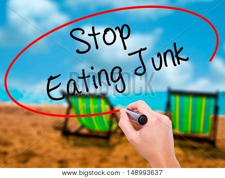 Man Hand Writing Stop Eating Junk With Black Marker On Visual Screen.