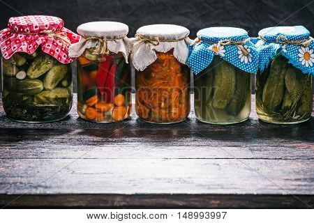Jars of pickles on the shelf in the dark cellar or pantry