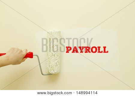 Hand writing PAYROLL word on a notebook with pen.