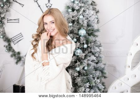 Beautiful Young Woman Wrapped In A Blanket Over Christmas Tree