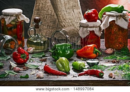 Jars of pickles on the table with vegetables and spices for preparing