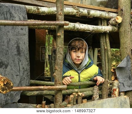 preteen boy in the autumn forest self made hut close up