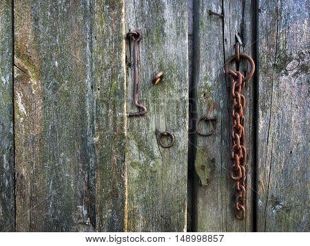 Vintage rusty locks close the old wooden door